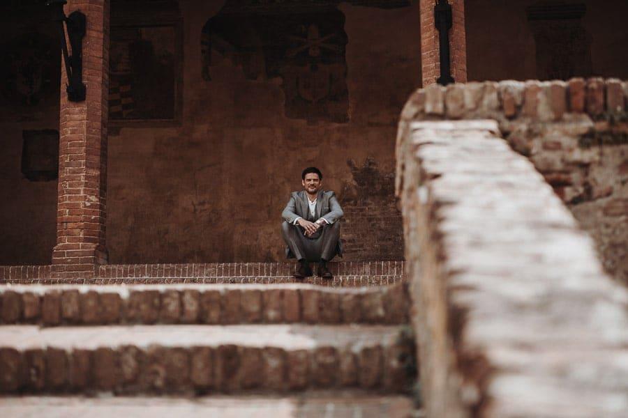 Bräutigam sitzt auf Stufe Toskana Hochzeit