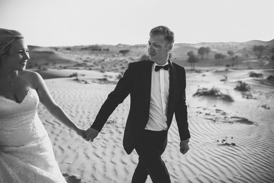 Bräutigam Hand in Hand mit Braut in der Wüste