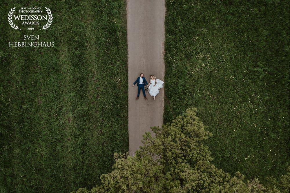 Brautpaar-liegt-auf-dem-boden-drohnenfotos-hochzeit-hochzeitsfotos-koeln