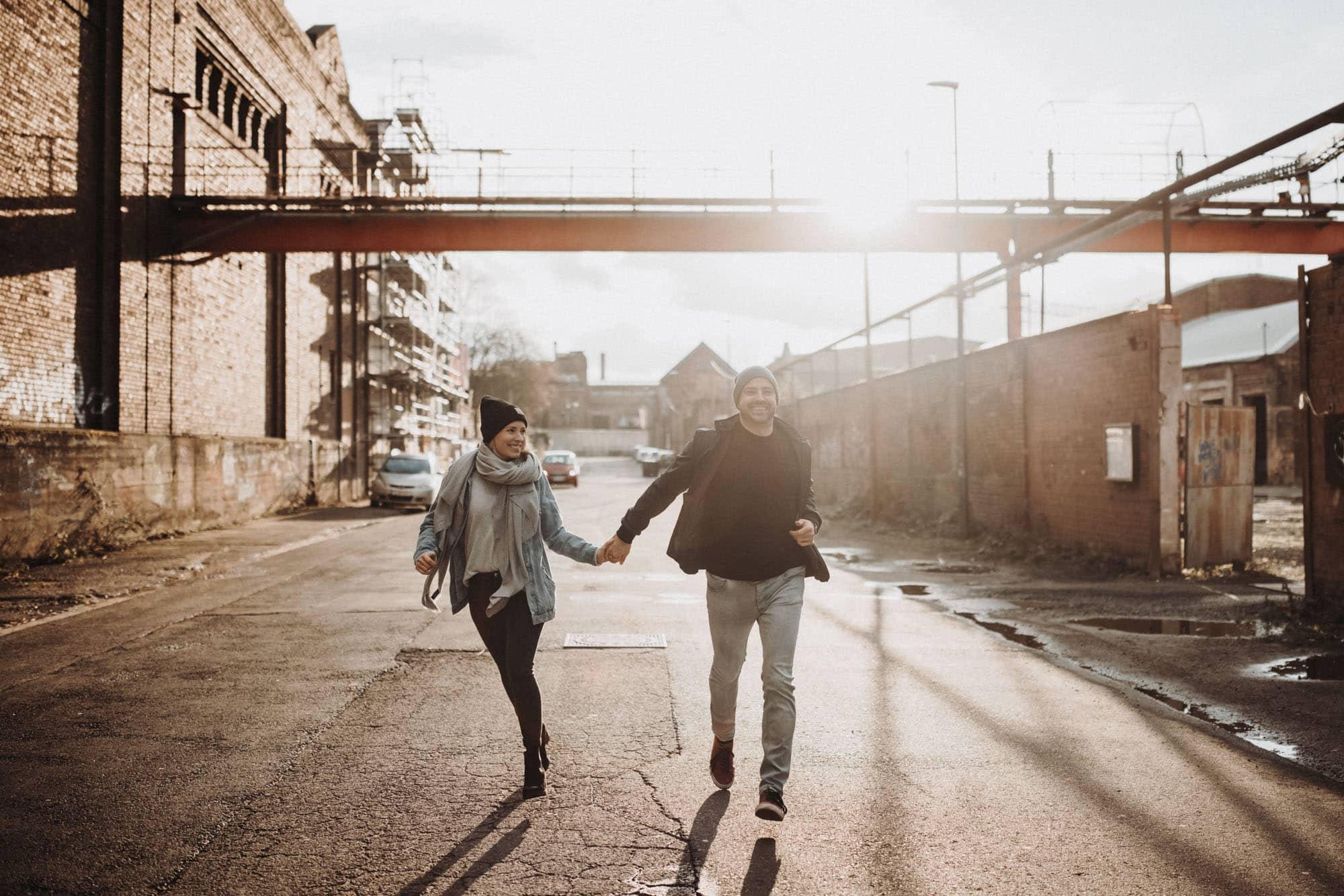 Paar-rennt-im-sonnenlicht-auf-Strasse